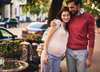 man and his pregnant wife happily walking | The 8 Most Incredible Pieces Of Advice For New Parents