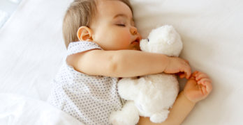 baby sleeping soundly while embracing white stuffed toy | 3 Tips To Establish A Baby Sleep Schedule In The First Year