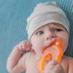 baby with orange teether in his mouth | When Do Babies Start Teething? 5 Effective Remedies To Help