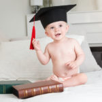 baby wearing graduation cap while sitting on a bed | How to Save Money For A Baby That's On The Way