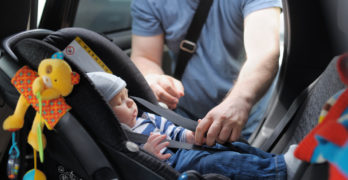 dad securing an infant car seat | How To Install An Infant Car Seat (Or Where To Get Help)