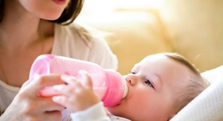 mom feeding her baby via a pink baby bottle | How to Wean a Baby: Everything You Need To Know
